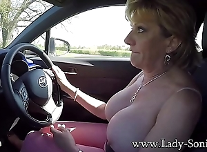 Mature blonde Lady Sonia plays here her tits while driving